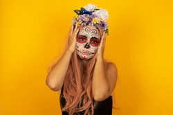 Portrait of beautiful young woman wearing halloween sugar skull make up  holding head in hands with unhappy expression watching sad movie about animals and trying not to cry.