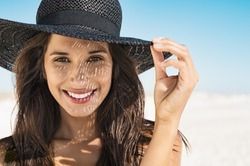 Portrait of beautiful young woman wearing summer black hat with large brim at beach. Closeup face of attractive girl with black straw hat. Happy latin woman smiling and looking at camera at sea.