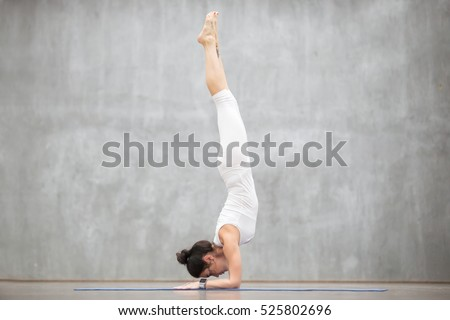 Portrait of beautiful young woman wearing white sportswear working out against grey wall, doing yoga or pilates exercise. Handstand feathered peacock pose, Pincha Mayurasana. Full length shot