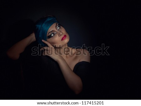 Portrait of beautiful young woman with blue scarf on black background. High fashion look.glamour portrait of beautiful sexy young female woman with red lips on black background with blue scarf.