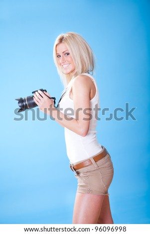 Portrait of beautiful young woman with camera on sky background