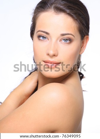 Portrait of beautiful young woman with clean skin looking at camera