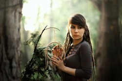 Portrait of beautiful young woman with dreadlocks in dark dress with traditional american indian amulet dreamcatcher in hands deep in forest. Back light. Ecofriendly concept. Close to nature lifestyle