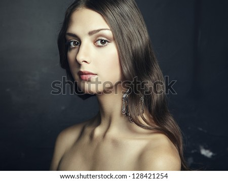 Portrait of beautiful young woman with earring. Fashion photo