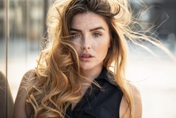 Portrait of beautiful young woman with freckles on her face , looking at camera. Girl with long hair and natural makeup.