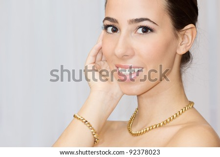 Portrait of beautiful young woman with golden jewelry  looking at camera.