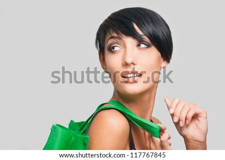 Portrait of beautiful young woman with green bag on gray background