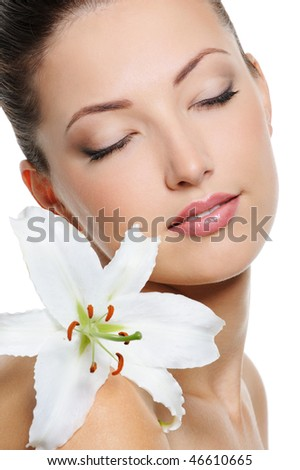 Portrait of beautiful young woman with health skin and with flower on her shoulder