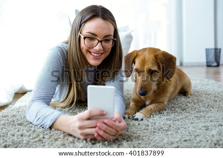 Shutterstock Portrait of beautiful young woman with her dog using mobile phone at home.