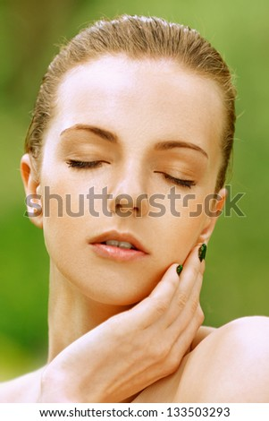 Portrait of beautiful young woman with her eyes closed, against green of summer park.