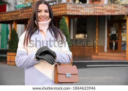 Portrait of beautiful young woman with leather gloves and stylish bag on city street Stock photo ©