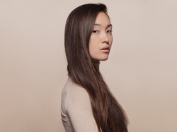 Portrait of beautiful young woman with long brown hair standing against beige background. Asian woman with a long straight hair looking at camera.