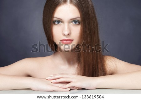 Portrait of beautiful young woman with long straight brown hair posing on black background