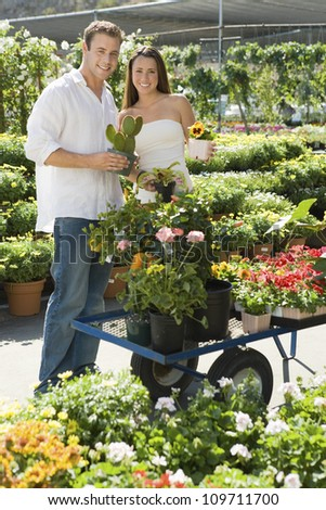 Portrait of beautiful young woman with man selecting plant at botanical garden