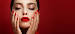 Portrait of beautiful young woman with perfect young skin, red matt lips and nails.  Model with bright scarlet color makeup and manicure posing on red background. Close up.