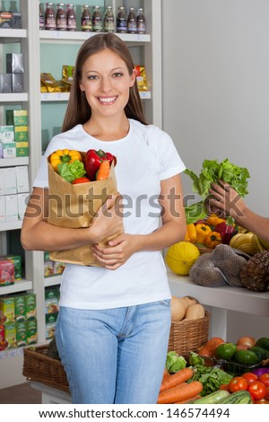 Portrait of beautiful young woman with vegetable bag in supermarket