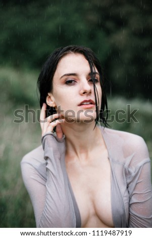 Portrait of beautiful young woman with wet hair in wet clothes under the summer rain. Sexy woman tilting her head to the side and feeling the rain falling on her face. Natural female beauty