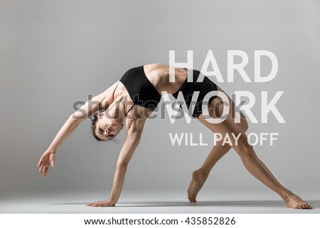 "Portrait of beautiful young woman working out in studio. Fit sporty girl doing backbend exercise. Camatkarasana, Wild Thing or Flip-the-Dog posture. Motivational text ""Hard work will pay off"""
