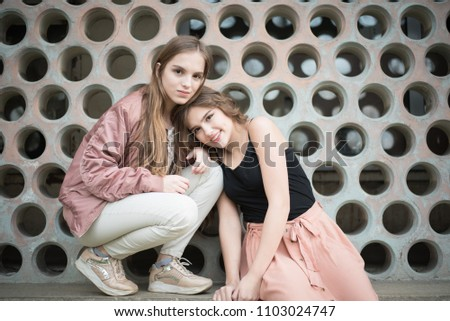 Portrait of beautiful young women looking at camera in the street.