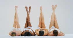 Portrait of beautiful young women of different ethnicities with perfect firm and slim bodies with hairless soft and silky legs crossed isolated on a white background.