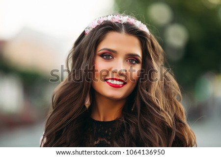 Portrait of beauty brunette with make up wearing flower diadem smiling at camera over blurred background. #1064136950