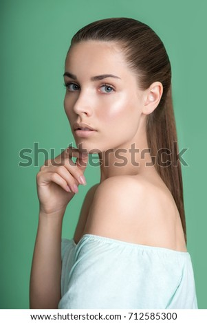 Portrait of beauty model with natural nude make up on green background. Beautiful young woman with clean perfect skin. Spa, skincare and wellness.  #712585300