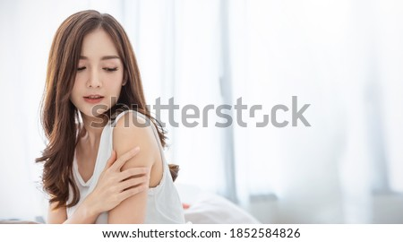 Portrait of beauty  smiling asian woman applying a lotion to her arm skin during her morning routine. Cute asian girl. Skincare body lotion, beauty clinic skincare spa, indoors woman lifestyle concept