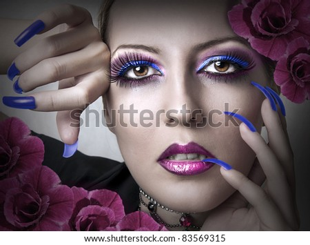 Portrait of beauty woman with fashion bright evening makeup and beauty purple manicure of fingernails and flowers. Female face closeup