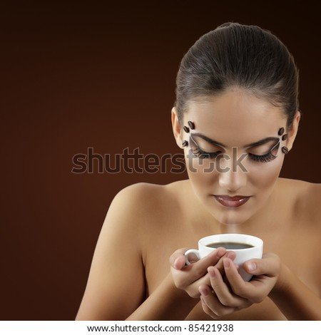 portrait of beauty young woman with beautiful brown make-up holding cup of coffee  isolated on brown background