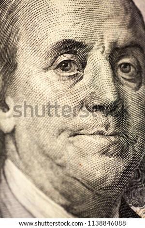 Ben Franklin face on us 100 dollar bill close up macro