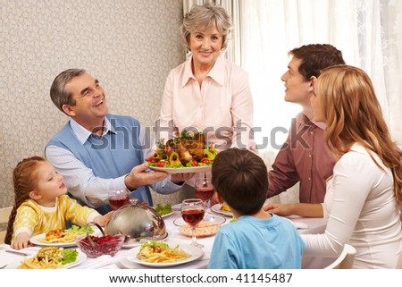 Portrait of big family at festive table looking at aged female with dish of delicious turkey