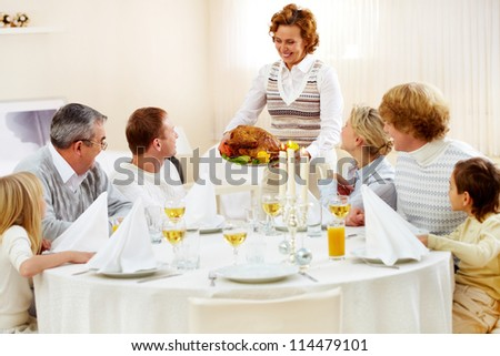Portrait of big family sitting at festive table and looking at aged female with dish of delicious turkey