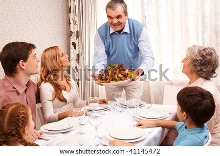 Portrait of big family sitting at festive table and looking at aged man with cooked turkey