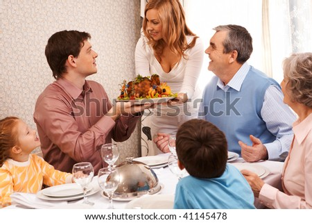 Portrait of big family sitting at festive table and looking at pretty female with dish of delicious turkey