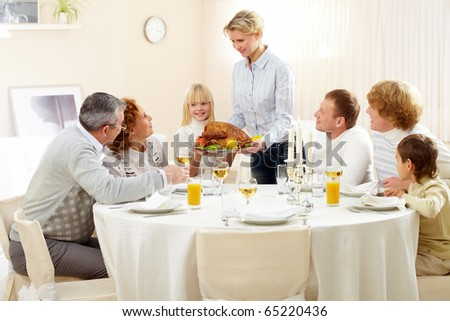 Portrait of big family sitting at festive table and looking at pretty woman with roasted turkey