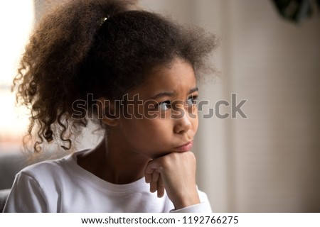 Portrait of black American child with thoughtful face hold hand under chin dreaming and looking away. Serious pensive black African lovely daughter sitting at home feeling boredom or have a question