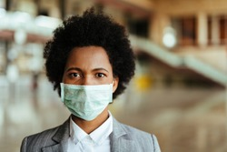 Portrait of black businesswoman wearing face mask during virus epidemic while standing at airport corridor.