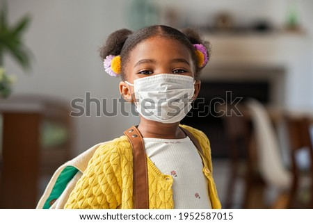 Portrait of black little girl wearing bagpack and covid-19 protective face mask ready for elementary school. African female child wearing surgical mask and looking at camera going back to primary.