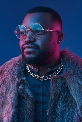 Portrait of black man with glasses and fur coat