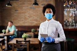 Portrait of black waitress wearing protective face mask while holding touchpad and looking at the camera in a pub.