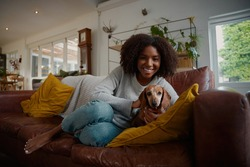 Portrait of black woman playing with pet dachshund dog at home sitting on couch