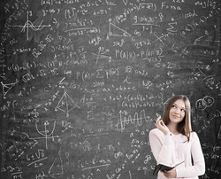 Portrait of blond girl solving a difficult task standing near blackboard with formulas. Concept of algebra. Mock up