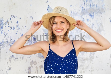 Portrait of blond in straw hat and blue dress, smiling Stock photo ©