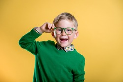 Portrait of blond little boy in green sweater and glasses. Kid at eye sight test. Stylish child holding glasses and looking at camera. Vision, eyesight measurement for school children. Back to school.