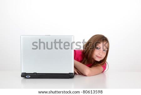 Portrait of blond little girl behind laptop computer