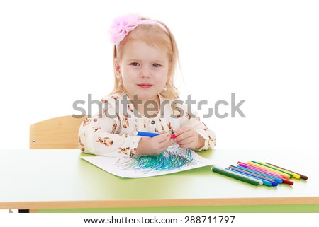 Portrait of blond little girl sitting at the table and draws markers-Isolated on white background