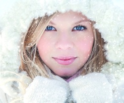 Portrait of blond pretty woman in fur coat at winter background