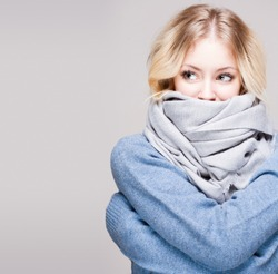 Portrait of blond winter beauty in light blue sweater and scarf.