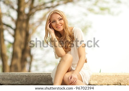 portrait of blond woman in white dress outdoor