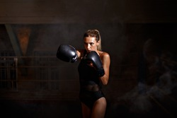 Portrait of blonde boxing girl in boxing gloves and body hitting pear.